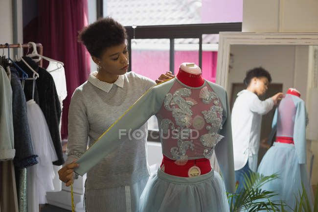 Fashion designer taking measurement of mannequin in fashion studio — Stock Photo