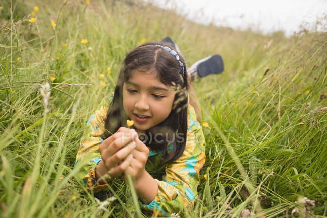 Menina segurando flor enquanto deitado na grama verde — Fotografia de Stock