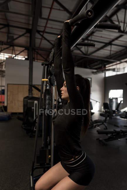 Bella donna che fa pull ups in palestra fitness — Foto stock