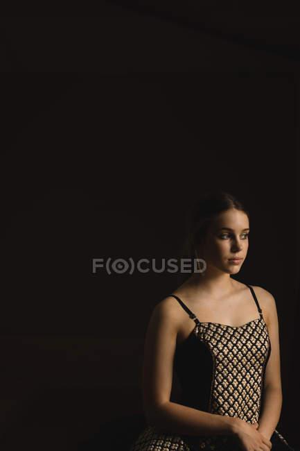 Bailarina pensativa mirando hacia otro lado sobre fondo negro - foto de stock