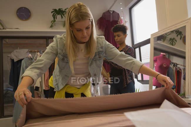 Belle créatrice de mode vérifiant tissu dans le studio de mode — Photo de stock