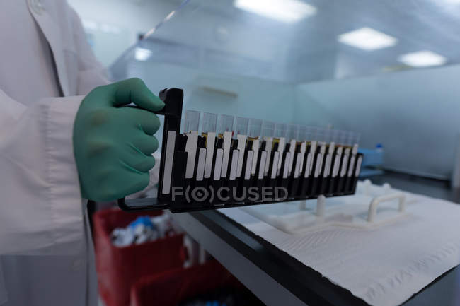 Laboratory technician holding test tubes in blood bank — Stock Photo