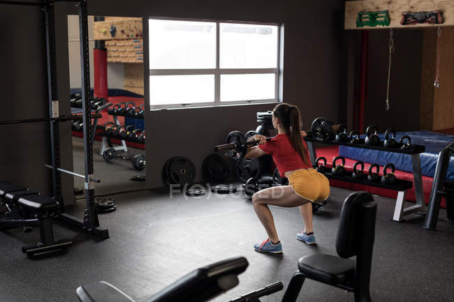Rear view of woman lifting barbell in fitness studio — Stock Photo