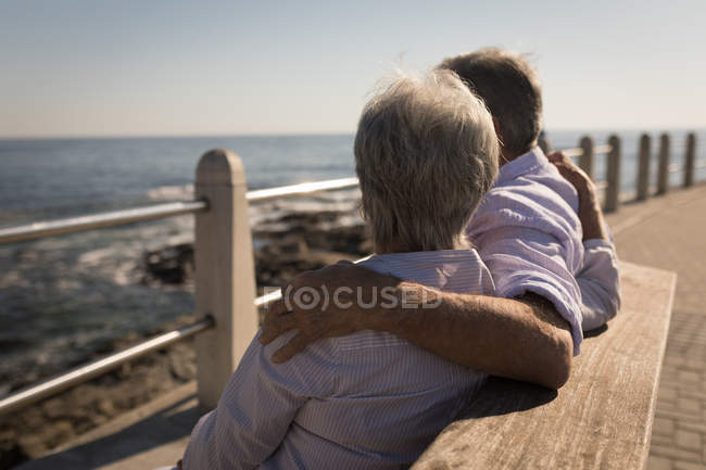 Senior couple sitting on bench with arms around at promenade — Stock Photo