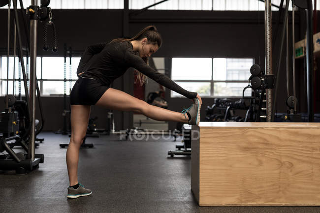 Fit woman doing stretching exercise in fitness studio — Stock Photo