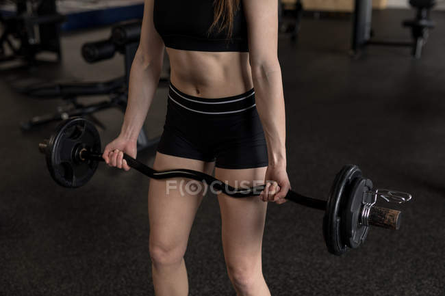 Mid section of woman lifting barbell in fitness studio — Stock Photo