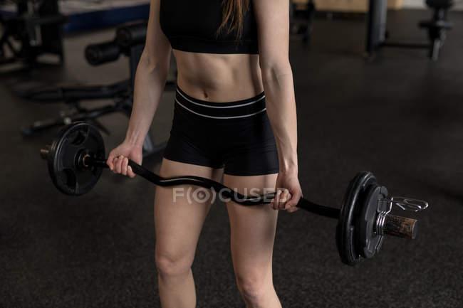 Mittleren Bereich der Frau anheben Langhantel im Fitness-studio — Stockfoto