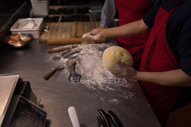 Panettiere mettere la farina bianca sulla pasta in panetteria — Foto stock