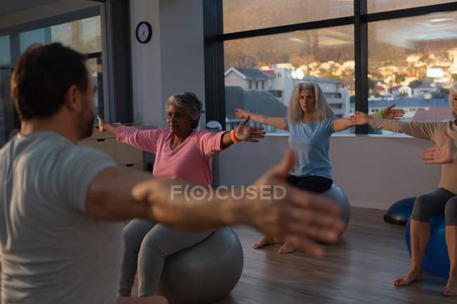Тренер и группа женщин старшего возраста, занимающихся йогой в центре йоги — стоковое фото