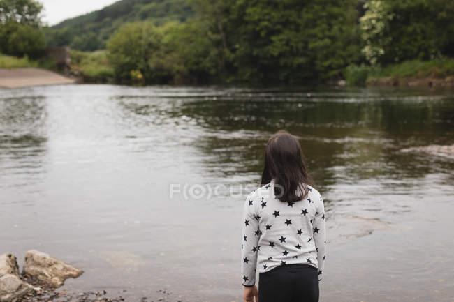 Visão traseira da menina de pé perto da ribeira — Fotografia de Stock