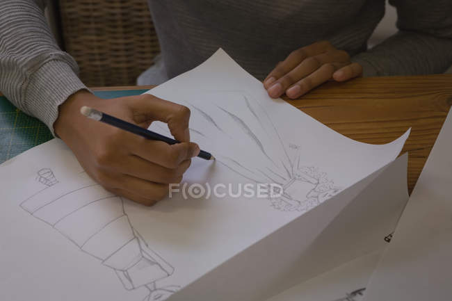 Close-up of fashion designer drawing sketch in fashion studio — Stock Photo