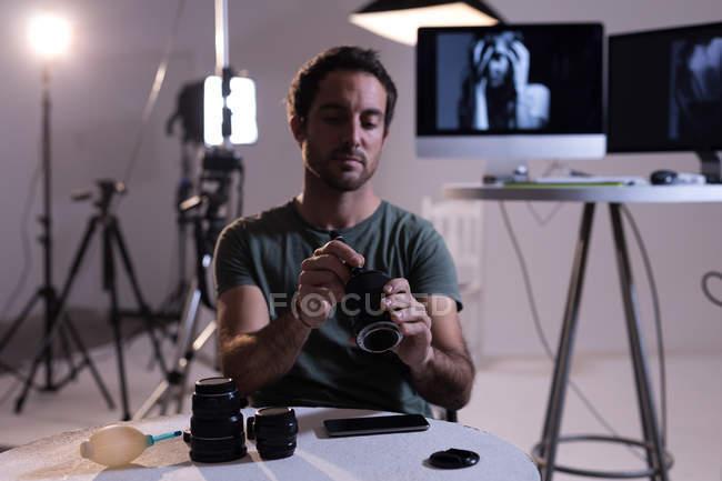 Fotógrafo masculino limpando a lente da câmera no estúdio de fotos — Fotografia de Stock