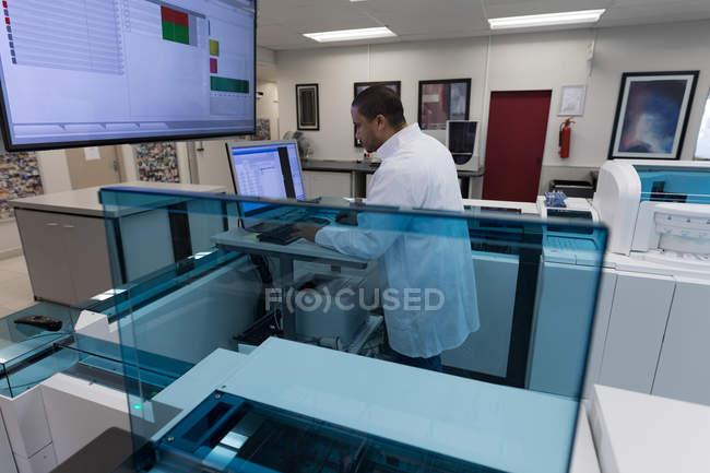 Technicien de laboratoire travaillant sur ordinateur — Photo de stock