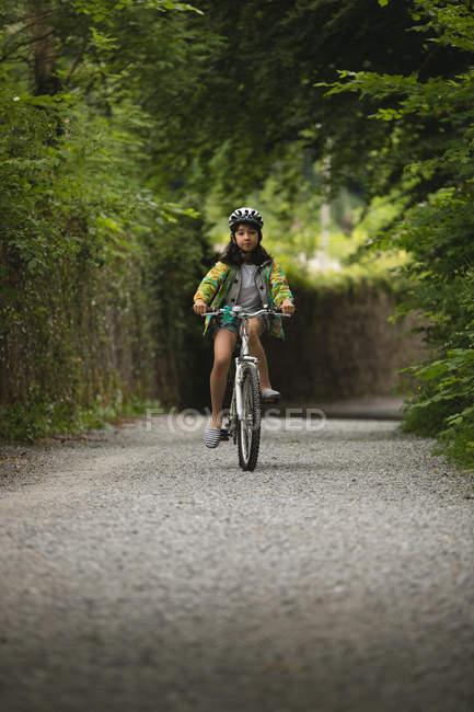 Молодая девушка на велосипеде по улице — стоковое фото