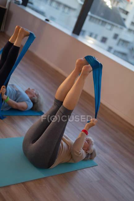 Gruppo di donne anziane che praticano yoga con una fascia di yoga nel centro yoga — Foto stock