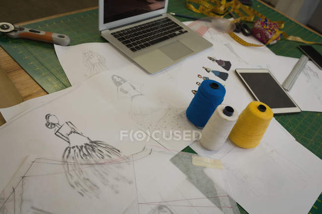Sketch, thread, laptop kept on table in fashion studio — Stock Photo