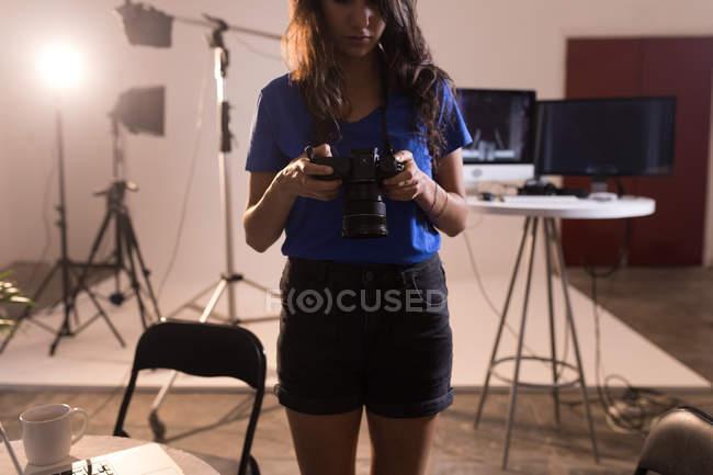 Modello femminile guardando la fotocamera digitale in studio fotografico — Foto stock