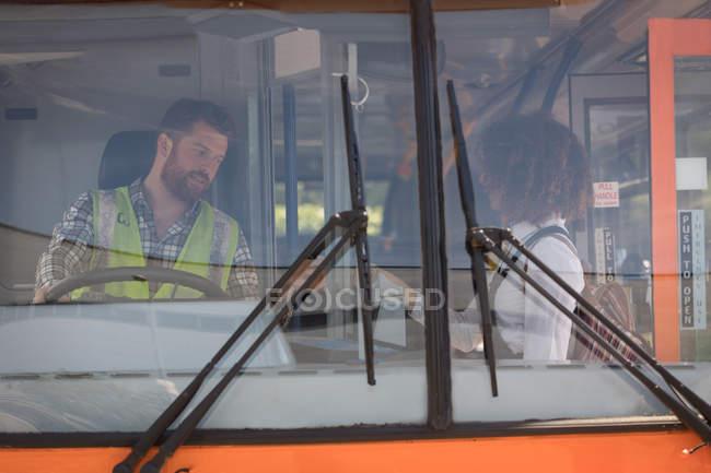 Молодые девушки пригородных принимает билет у водителя в современный автобус — стоковое фото