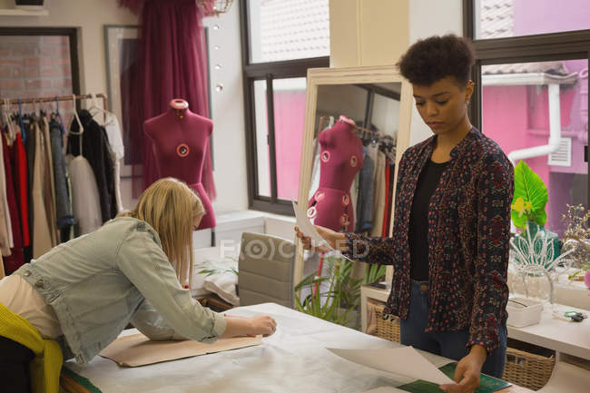 Fashion designer working on table in fashion studio — Stock Photo