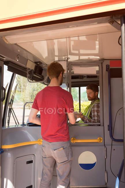Молодые мужчины пригородных принимает билет у водителя в современный автобус — стоковое фото