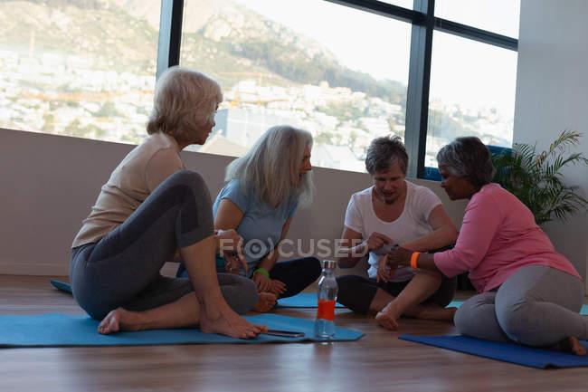 Groupe des femmes âgées utilisation montre intelligente dans le centre d'yoga — Photo de stock
