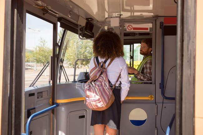 Вид сзади женского пригородных принимает билет у водителя в современный автобус — стоковое фото