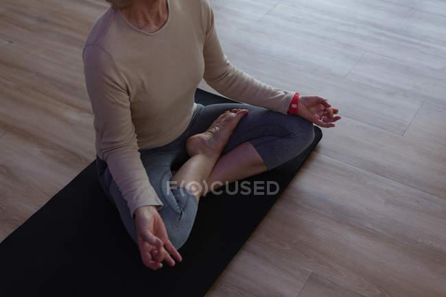 Senior woman performing yoga in yoga center — Stock Photo