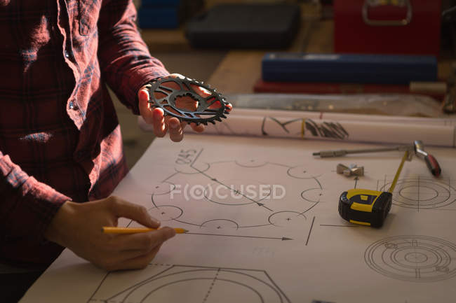 Mid section of mechanic drawing on paper at table in workshop — Stock Photo