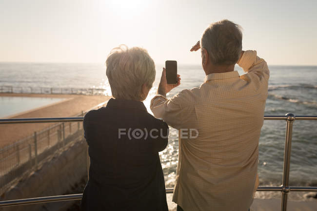 Rear view of senior couple using mobile phone near sea side on a sunny day — Stock Photo