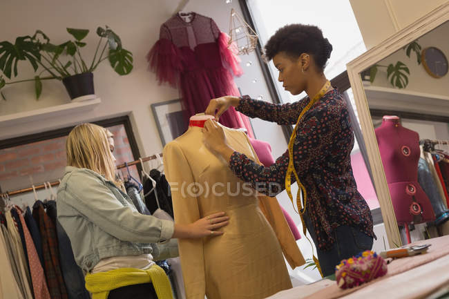 Fashion designer dressing mannequin in fashion studios — Stock Photo