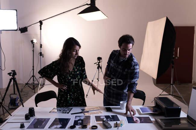 Fotografo di sesso maschile e femminile che discute di fotografie in studio fotografico — Foto stock