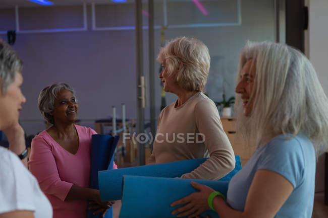 Группа старших женщин, взаимодействующих друг с другом в центр йоги — стоковое фото