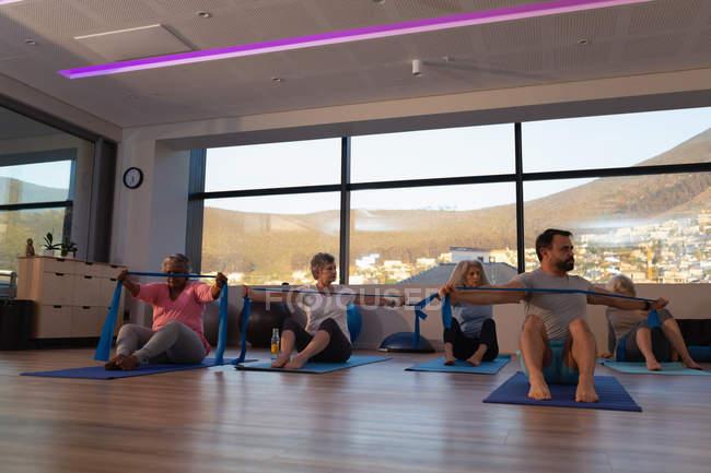 Allenatore e gruppo di donne anziane che praticano yoga nel centro yoga — Foto stock