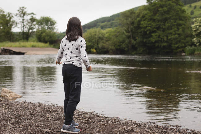 Young girl standing near riverside — Stock Photo