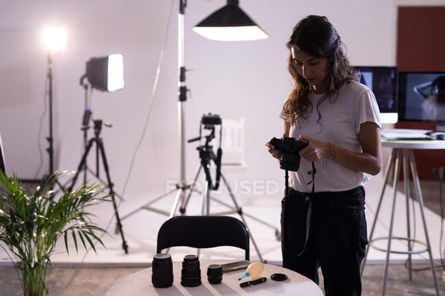 Женская модель просматривает фотографии на цифровой камере в фотостудии — стоковое фото