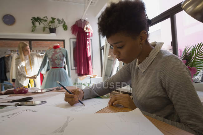 Fashion designer drawing sketch in fashion studio — Stock Photo