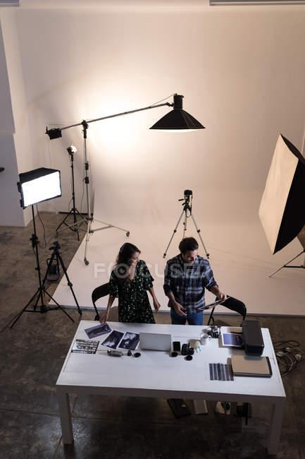 Fotografo maschio e femmina che guarda fotografie in studio fotografico — Foto stock