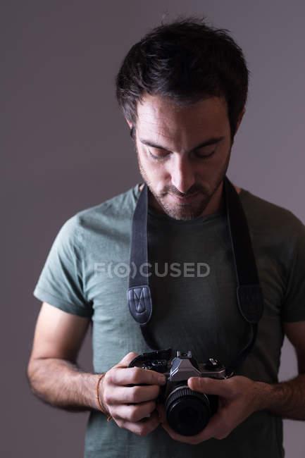 Мужской фотограф, стоящий с цифровой камерой в фотостудии — стоковое фото