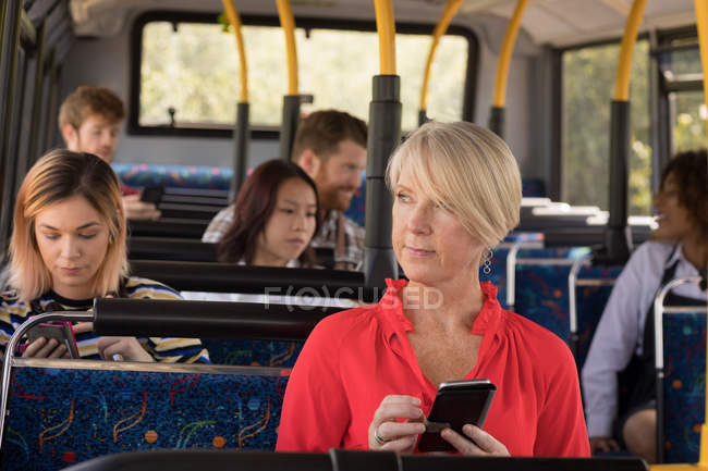 Thoughtful female commuter using mobile phone while travelling in modern bus — Stock Photo