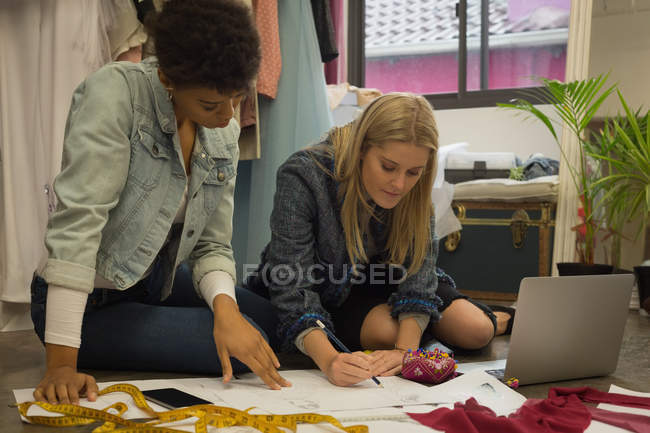Beautiful fashion designers drawing a sketch in fashion studio — Stock Photo