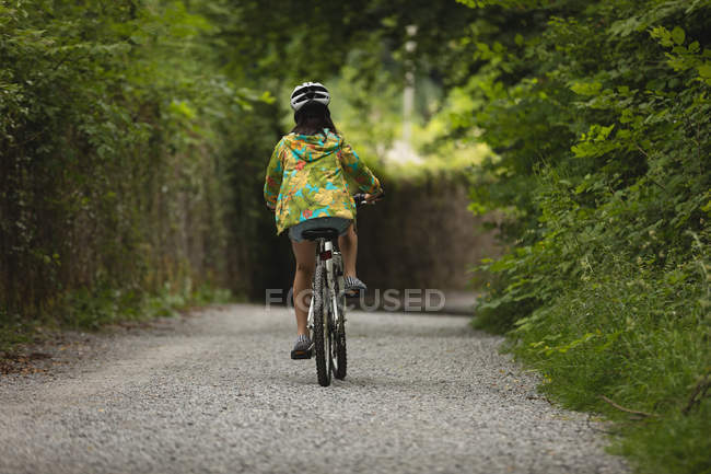 Rear view of girl riding bicycle on street — Stock Photo