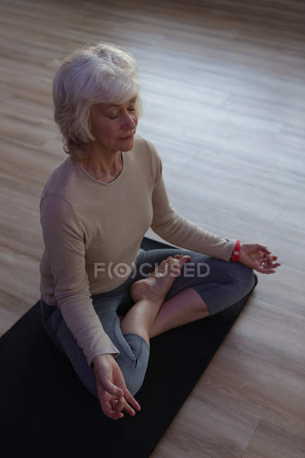 Senior mujer realizar yoga en centro de yoga - foto de stock