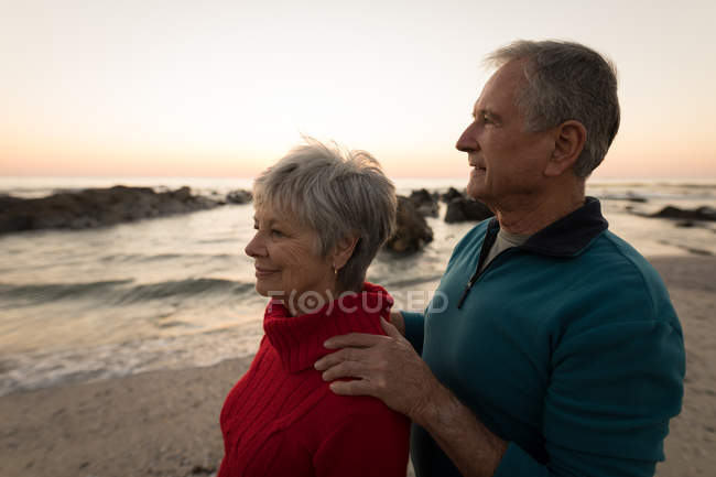 Close-up of senior couple standing on beach during sunset — Stock Photo