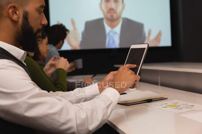 Businessman using digital tablet in conference room at office — Stock Photo