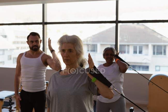 Тренер, инструктируя группа старших женщин при выполнении упражнений в центр йоги — стоковое фото