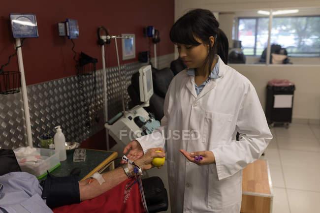 Médico verificando o homem sênior doando sangue no banco de sangue — Fotografia de Stock