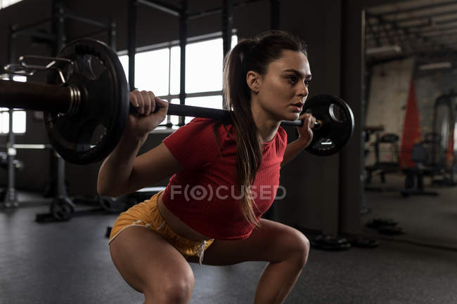 Beautiful woman doing a barbell squat in fitness studio — Stock Photo