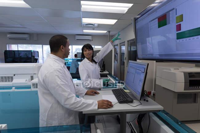 Лаборанты обсуждают на дисплее в банке крови — стоковое фото