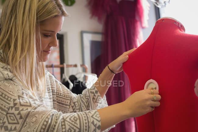 Fashion designer dressing mannequin in fashion studio — Stock Photo