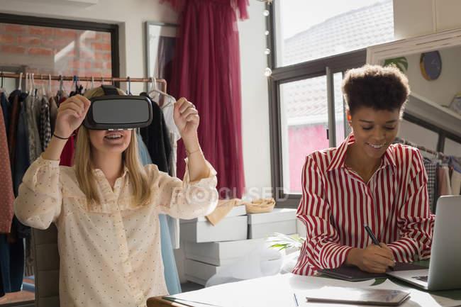 Créateurs de mode utilisant casque de réalité virtuelle et tablette graphique dans le studio de mode — Photo de stock